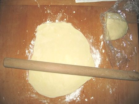 のし台でうどん生地を麺棒で伸ばす図
